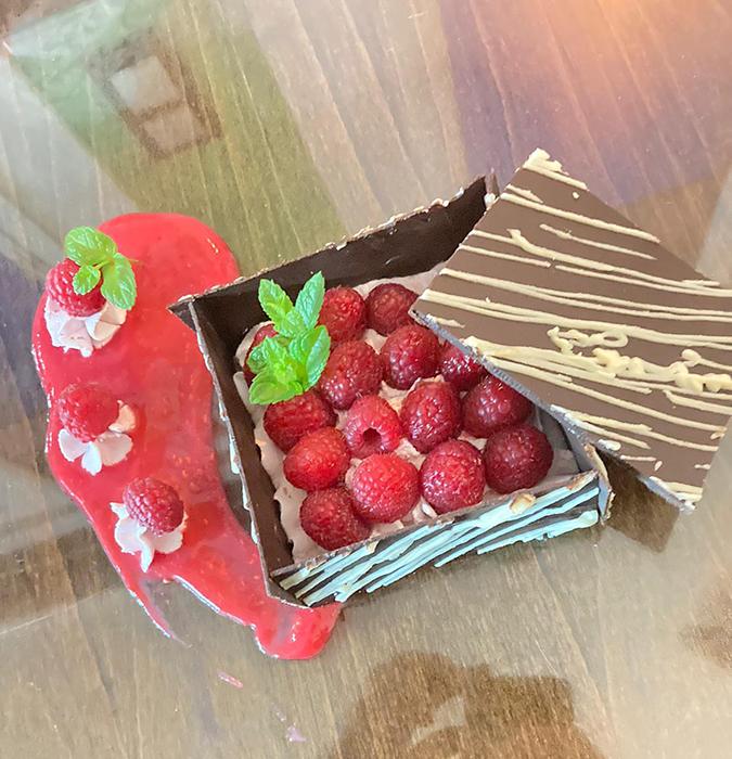 Emplate de caja de chocolate con nata de frambuesa adornada con hojitas de menta
