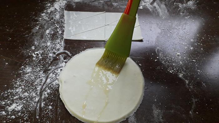 Untando huevo a las láminas de hojaldre