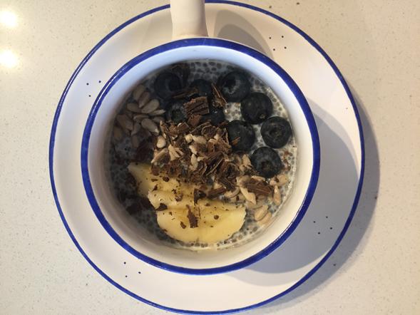 Tazón con semillas de chía, arándanos, ralladura de chocolate, pipas y platano